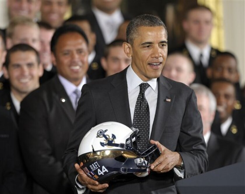 "President Barack Obama holds a Navy football team helmet in the East Room of the White House in Washington, Friday, April 12, 2013, after presenting the Commander-in-Chief Trophy to the United States Naval Academy football team. Head coach Ken Niumatalolo watches at left. The helmet bears a ""44"" st"