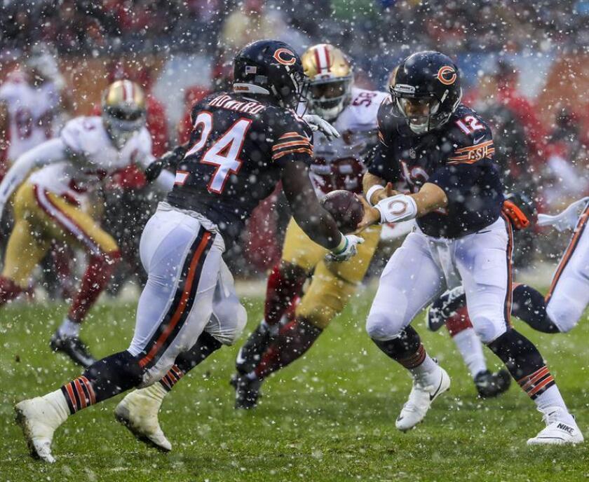 El mariscal de campo de los Bears de Chicago Matt Barkley (d) envía una bola a su compañero Jordan Howard (i) durante un partido de la NFL frente a los 49ers de San Francisco, disputado en el Soldier Field de Chicago, Illinois (EE.UU.), este 4 de diciembre de 2016. EFE