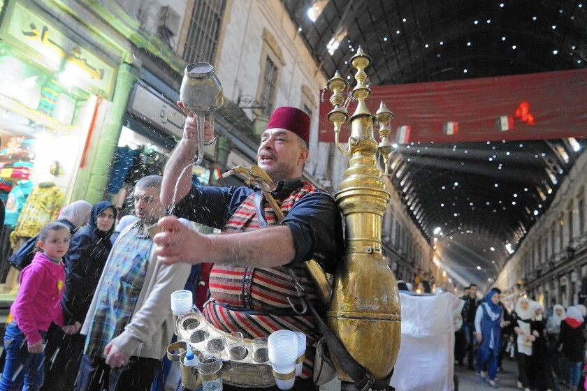 Isahak Kraymeen sells tamarind juice at the Hamidiya souk in Damascus, Syria.
