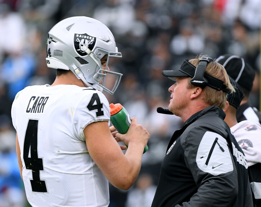 Raiders coach Jon Gruden speaks to quarterback Derek Carr during win over Chargers last year in Carson.