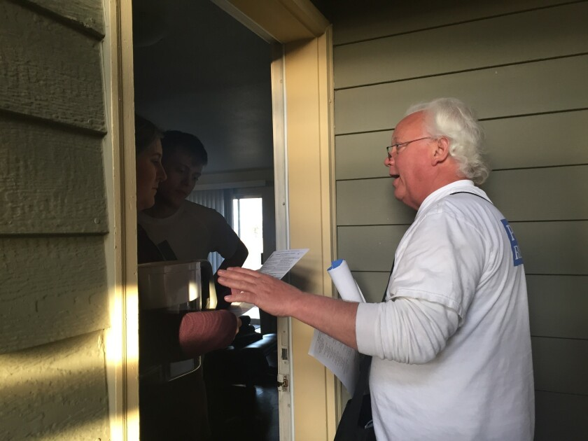 Doug Smithson, a volunteer for the Bernie Sanders campaign, speaks to Caitlyn Long and Tyler Yager in Reno about supporting Sanders in Nevada's Democratic caucuses on Feb. 20.