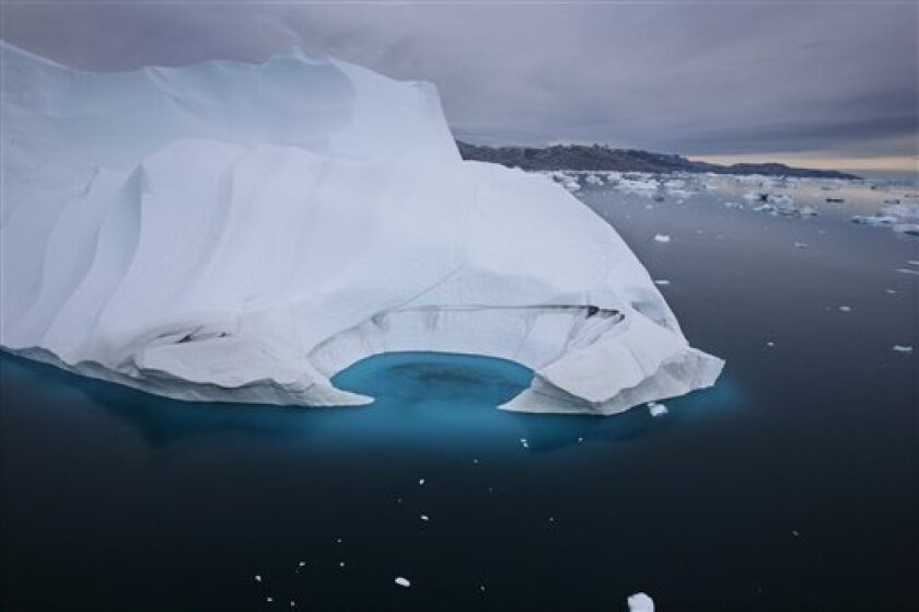FILE - In this July 19, 2007 file photo, an iceberg is seen melting off the coast of Ammasalik, Greenland.  A new assessment of climate change in the Arctic shows the ice in the region is melting faster than previously thought and sharply raises projections of global sea level rise this century. (A