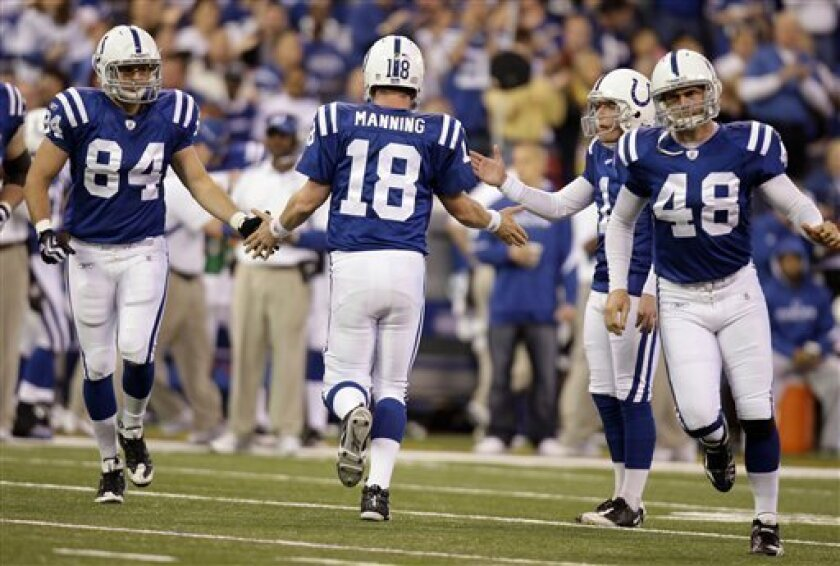 Indianapolis Colts quarterback Peyton Manning (18) is congratulated by tight end Jacob Tamme (84), kicker Pat McAfee, and tight end Justin Snow (48) after the Colts scored a touchdown against the Tennessee Titans in the first quarter of an NFL football game in Indianapolis, Sunday, Dec. 6, 2009. The Colts defeated the Titans 27-17. (AP Photo/Michael Conroy)