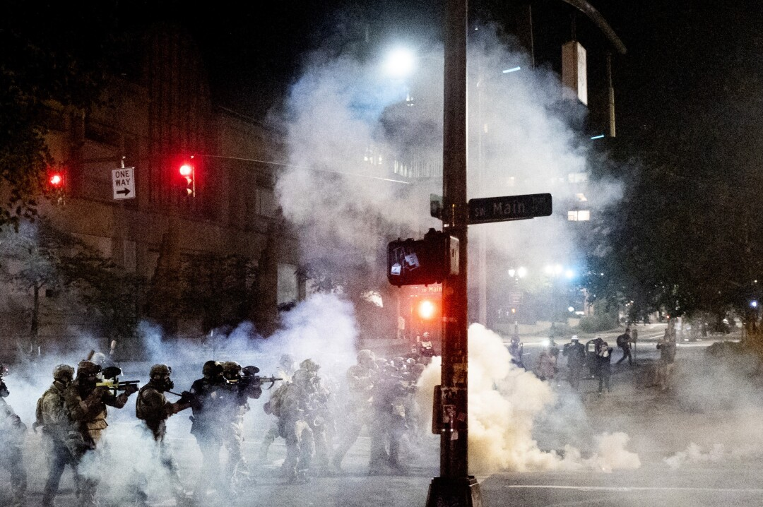 Federal agents try to disperse protesters.