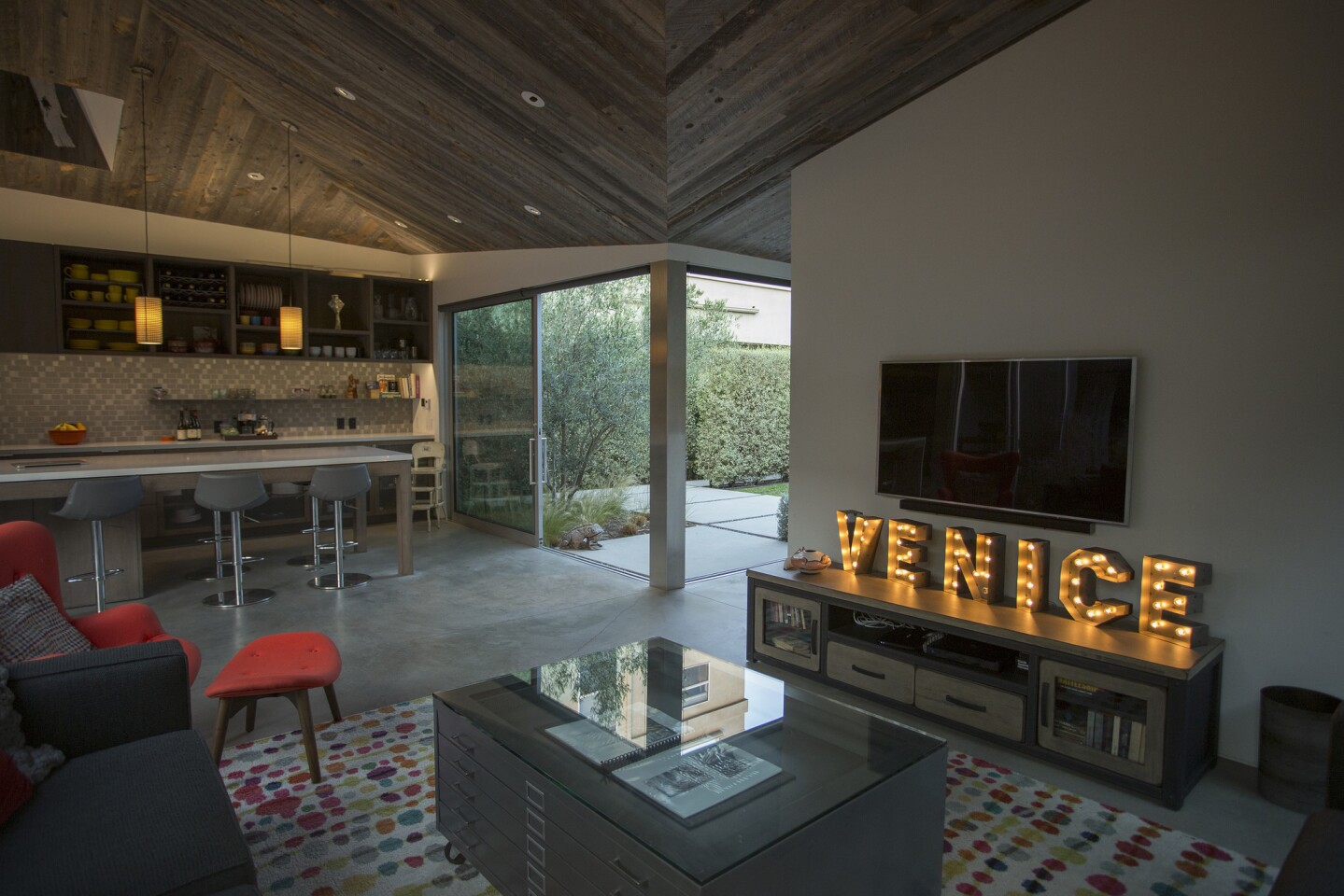 A view from the living area into the dining and kitchen areas and the front yard of the duplex.