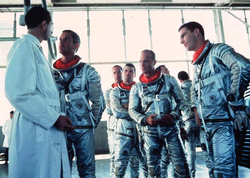 Scott Glenn as Alan Shepherd confronts a NASA scientist about changes to the Mercury capsule while the other astronauts (Charles Frank as Scott Carpenter, Fred Ward as Gus Grissom, Ed Harris as John Glenn and Dennis Quaid as Gordon Cooper) provide moral support.