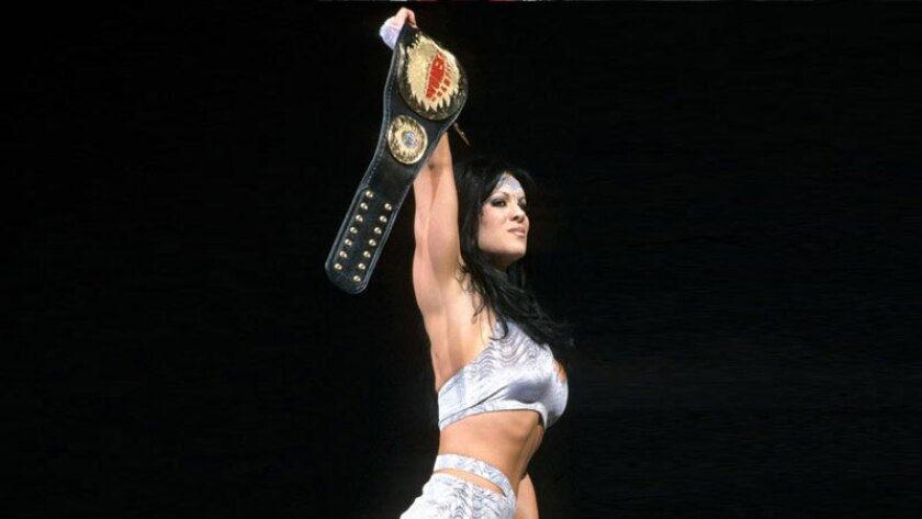 Chyna holds up her WWE women's championship belt in 2000.