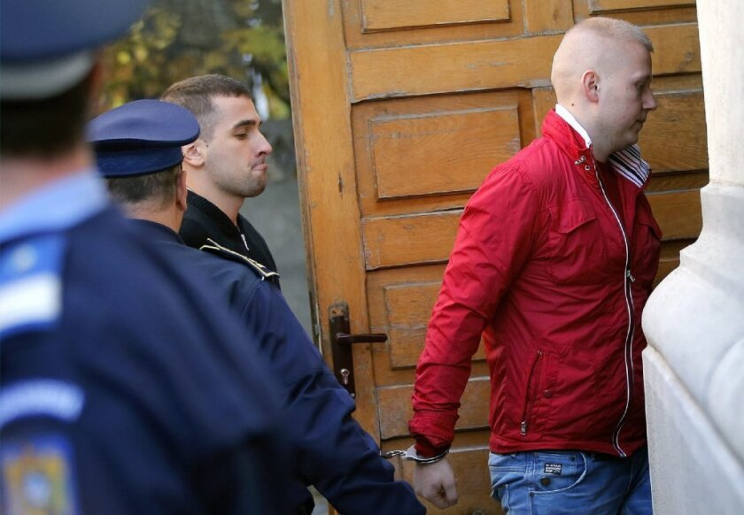 Art theft suspects Eugen Darie, right, and Radu Dogaru are escorted by police as they arrive handcuffed at a courthouse in Bucharest, Romania.
