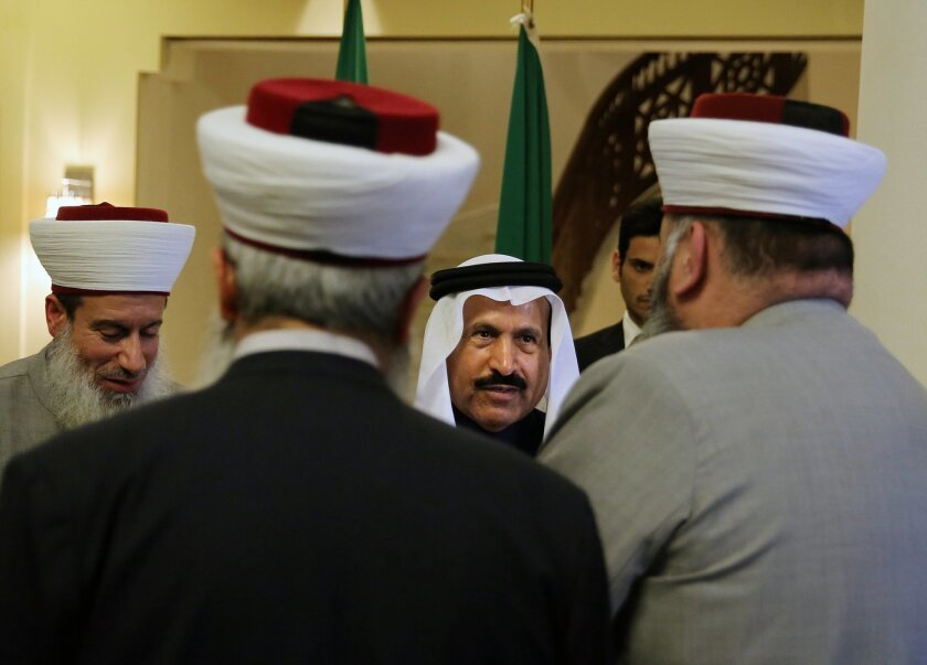 In this Wednesday, Feb. 24, 2016 photo, Saudi Ambassador to Lebanon Ali Awad Assiri, center, receives Sunni clerics during their visit to express their solidarity with the Kingdom of Saudi Arabia, at the Saudi Embassy in Beirut, Lebanon. Lebanon is getting hammered by punishments from a furious Saudi Arabia, which has cut off billions in aid and told its citizens not to visit the country, in an escalating diplomatic crisis that was prompted by Beirut's siding with Iran against the kingdom and that now threatens to wreck Lebanon's fragile economy. (AP Photo/Bilal Hussein)