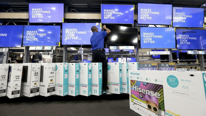 An employee adjusts a television display at a Best Buy store in Cary, N.C.
