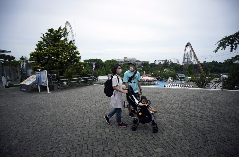 A family walks at the newly-reopened Yomiuriland amusement park in Tokyo Tuesday, June 16, 2020. The park has been closed since the end of March as a part of the precautions to help curb the spread of the coronavirus. (AP Photo/Eugene Hoshiko)