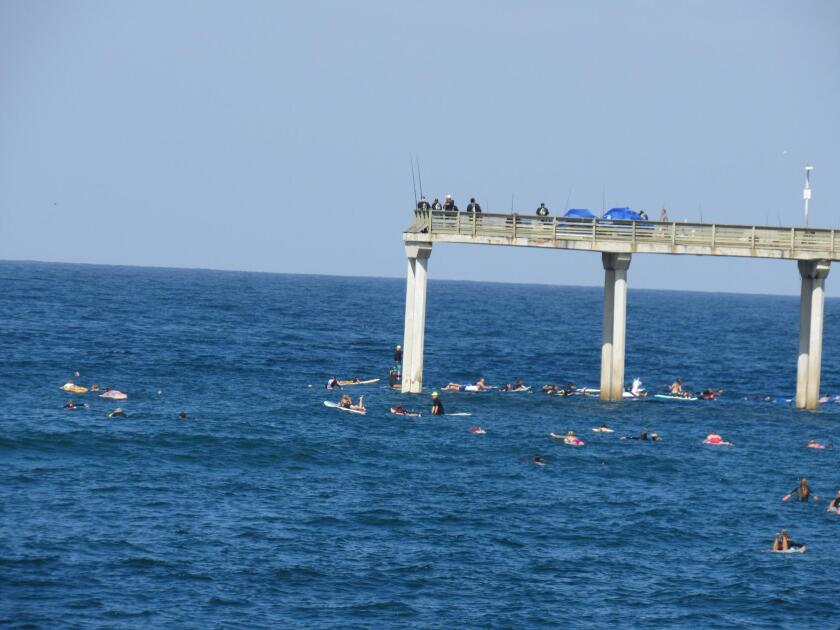 Fishermen on the pier share the spot with surfers in the water below.