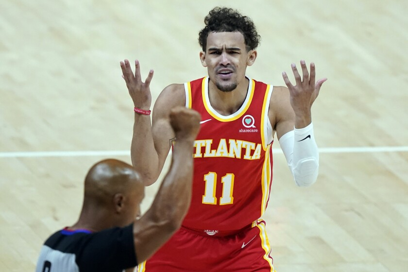 FILE - In this June 27, 2021, file photo, Atlanta Hawks' Trae Young (11) disputes a foul called by a referee during the first half of Game 3 of the NBA Eastern Conference basketball finals against the Milwaukee Bucks in Atlanta. Players like Atlanta's Trae Young will have a tougher time drawing foul calls this season, with the NBA cracking down on non-basketball moves offensive players used to make to create contact with defenders. (AP Photo/Brynn Anderson, File)