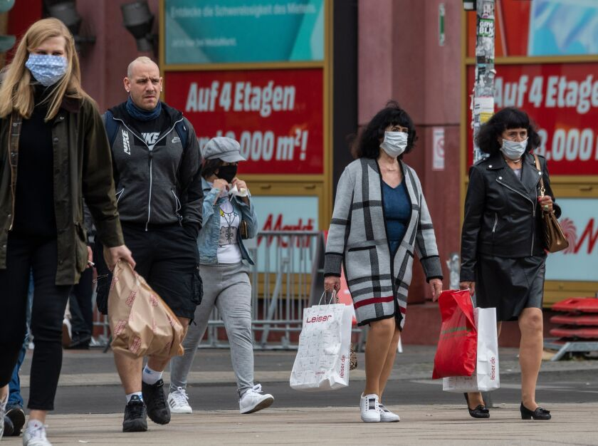 Shoppers wearing face masks walk out of a shopping mall in Berlin
