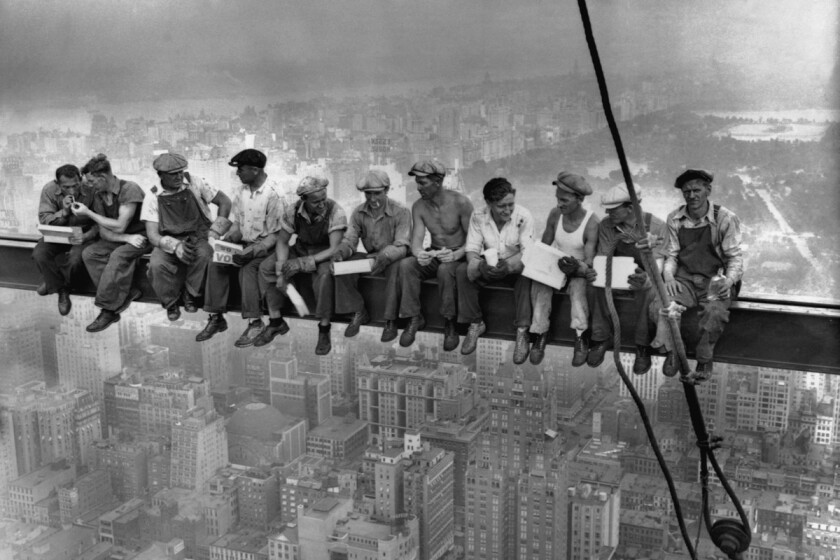 An iconic 1932 photo of construction workers eating their lunches atop a steel beam 800 feet above ground, at the building site of the RCA Building in Rockefeller Center.