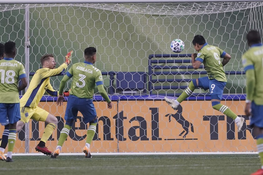 Seattle Sounders forward Raul Ruidiaz (9) scores a goal against Vancouver Whitecaps goalkeeper Bryan Meredith, second from left, during the second half of an MLS soccer match Saturday, Oct. 3, 2020, in Seattle. The Sounders won 3-1. (AP Photo/Ted S. Warren)