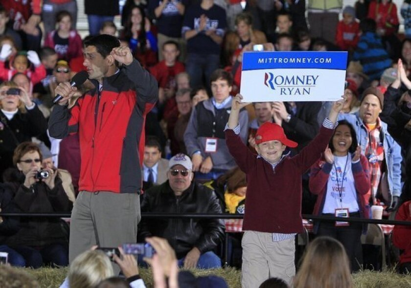 Republican vice presidential candidate Paul Ryan speaks during a campaign stop in Yellow Springs, Ohio, as his son Charlie jumps on stage with a sign.