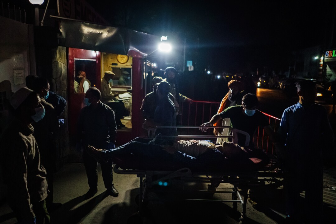 Medical workers help bring in a wounded patient brought by an ambulance to a hospital in Kabul