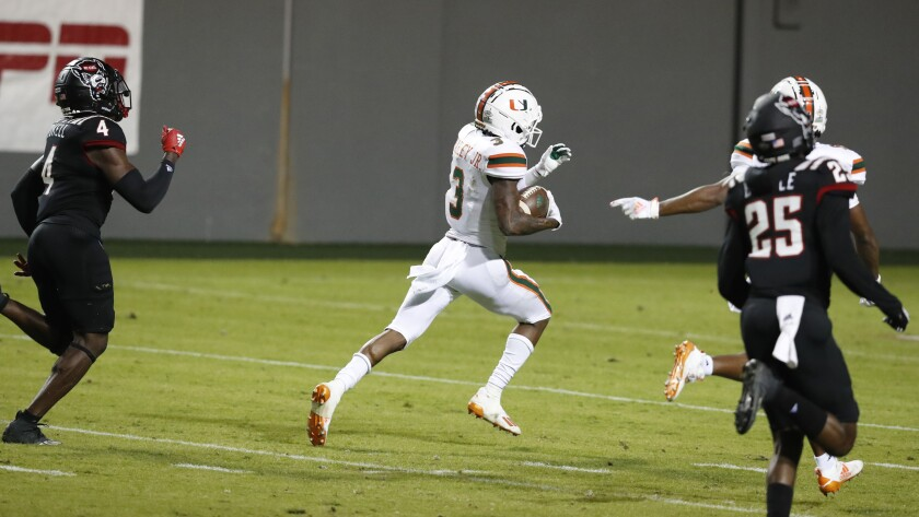 Miami wide receiver Mike Harley (3) runs on a 54-yard touchdown reception as North Carolina State cornerback Cecil Powell (4) trails during the second half of an NCAA college football game Friday, Nov. 6, 2020, in Raleigh, N.C. (Ethan Hyman/The News & Observer via AP, Pool)