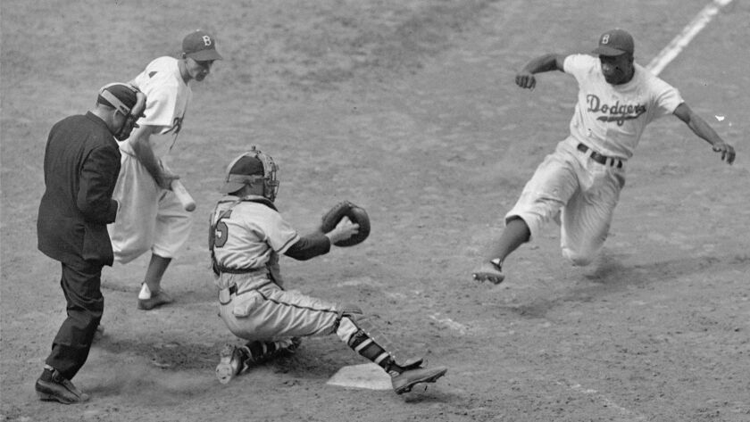 The Brooklyn Dodgers' Jackie Robinson steals home as Boston Braves catcher Bill Salkeld is thrown of