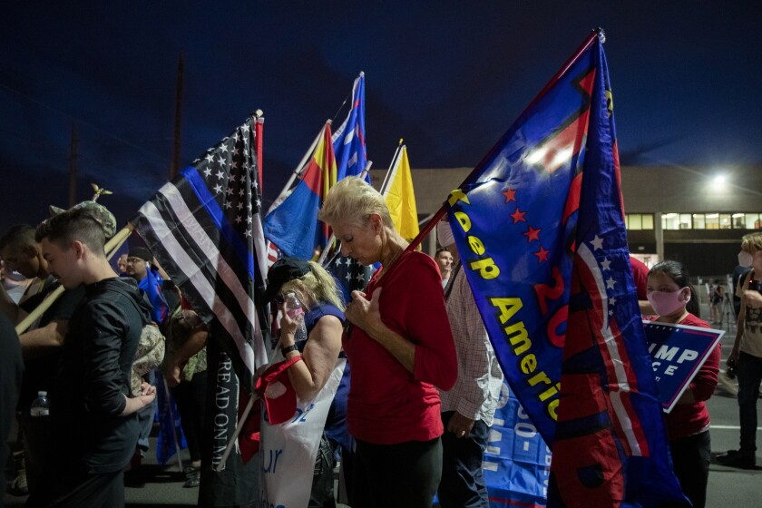 Trump supporters bow their heads in prayer while protesting in the parking lot at the Maricopa County