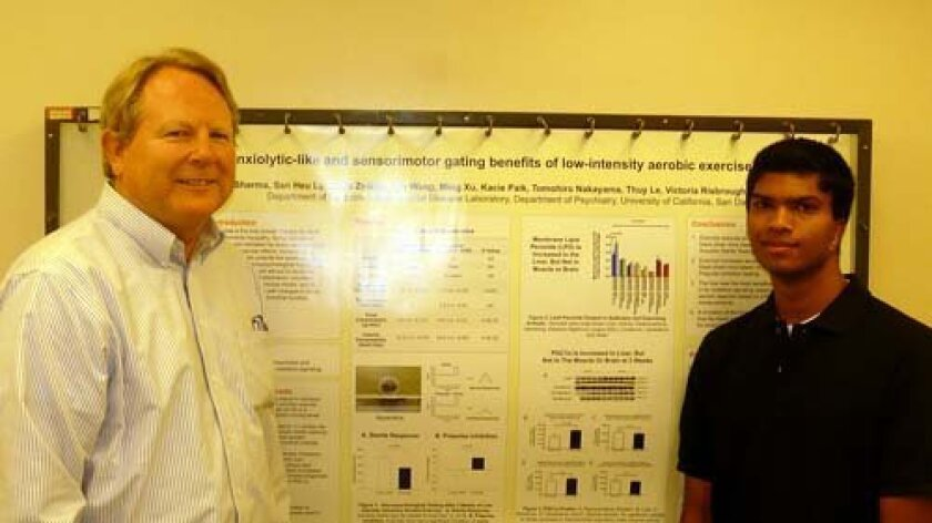 Varun Sharma stands with Robert Naviux, one of his mentors, in front of the poster he presented at the conference. Photo: Courtesy