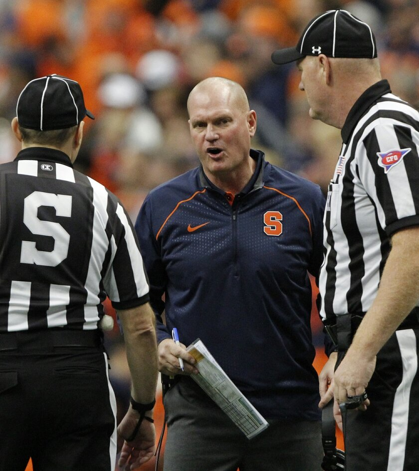 FILE - In this Oct. 24, 2015, file photo, Syracuse head coach Scott Shafer talks with officials about a play in the second quarter of an NCAA college football game against Pittsburgh in Syracuse, N.Y. The ACC has a system in place for coaches to help monitor officials who call their games, and over