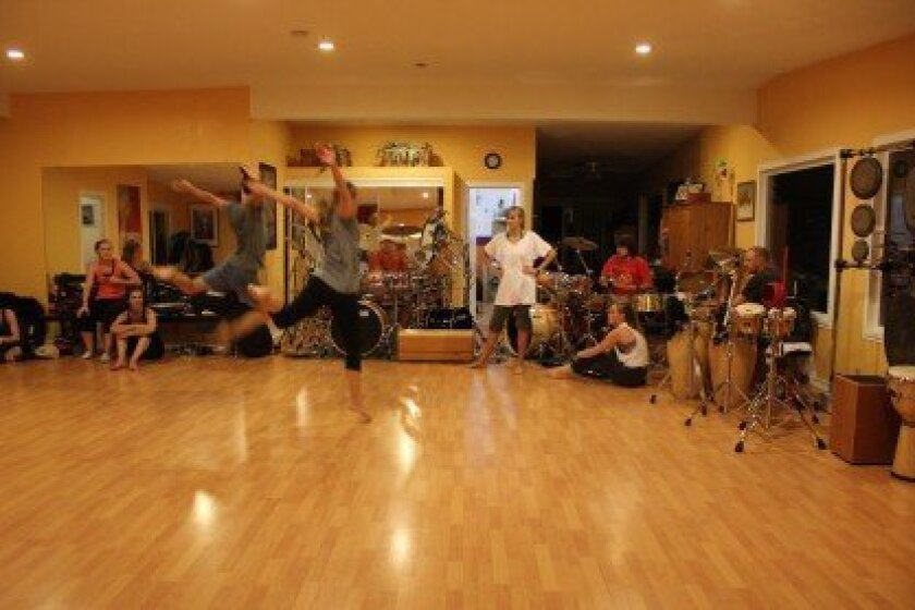 Faith Jensen-Ismay, artistic director of the Mojalet Dance Collective, looks on as two of the company's dancers rehearse one of their routines, as members of Rhythm Talk play drums and percussion. The rehearsal took place at the studio in Jensen-Ismay's Poway home.
