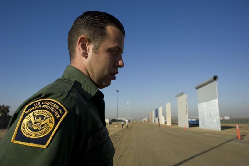 Un agente del servicio de patrulla fronteriza de EE.UU. junto a prototipos del muro fronterizo entre EE.UU. y México. EFE/Archivo