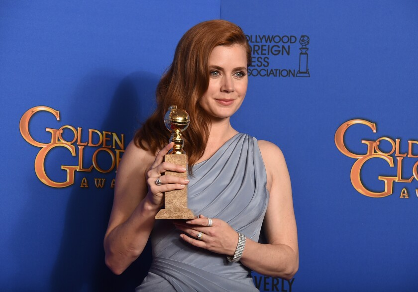 "Amy Adams poses in the press room with the award for lead actress in a comedy or musical motion picture for ""Big Eyes."""