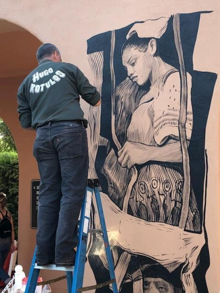 Hugo Crosthwaite works on one of his new murals at Liberty Station in Point Loma