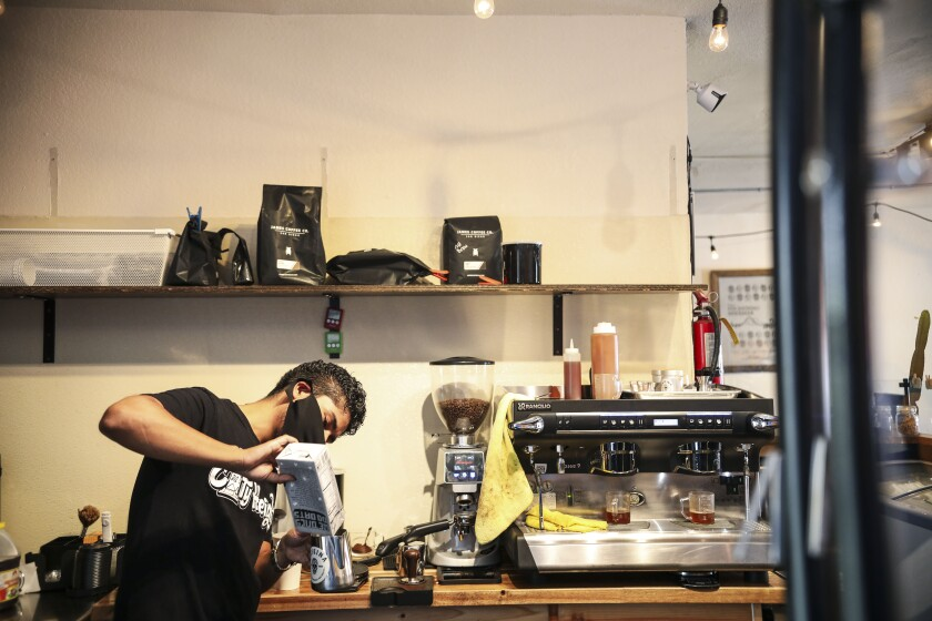 Andrew Benavides, owner of Cafeina Cafe, makes coffee drinks for customers in City Heights on Tuesday, July 28, 2020.