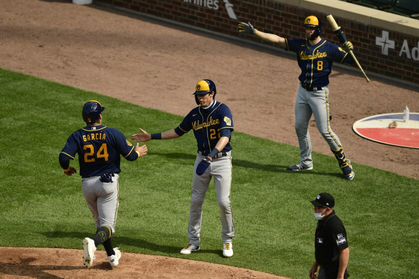 Milwaukee Brewers' Avisail Garcia (24) celebrates with teammates Christian Yelich (22) and Ryan Braun (8) after scoring on a Justin Smoak two RBI double during the fourth inning of a baseball game against the Chicago Cubs Saturday, Aug. 15, 2020, in Chicago. (AP Photo/Paul Beaty)