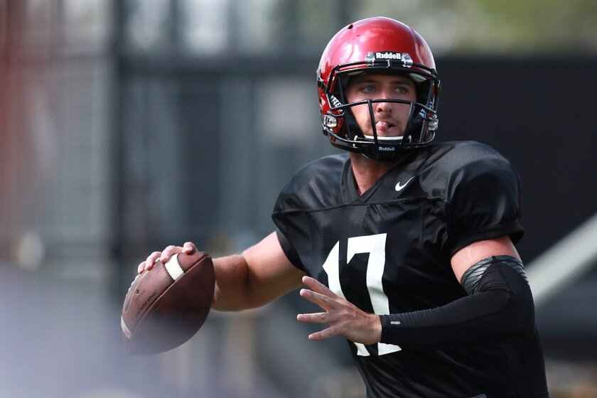 Aztec quarterback Maxwell Smith looks for an opening while running plays at practice.