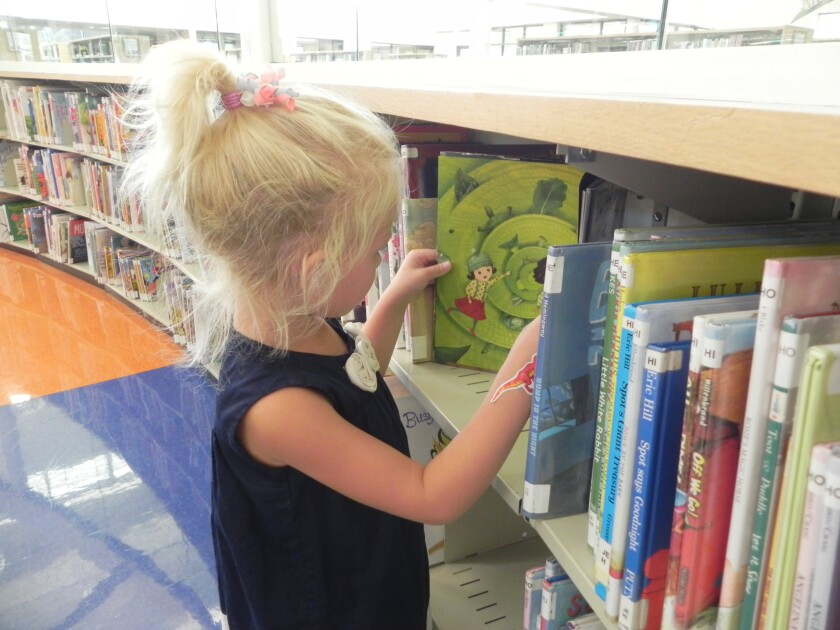 Vida Adomitis, 4 year old picking out a book to check-out with Mom, Tahnee Adomitis.jpg