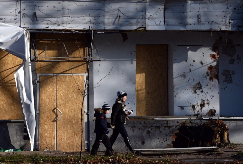 A woman and a child walk past a damaged building in the eastern Ukrainian city of Donetsk on Dec. 14. Russia's March annexation of Crimea triggered rebellions in eastern Ukraine that continue.