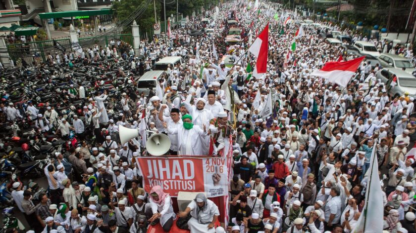 Protesters march in Jakarta, Indonesia, to demand the city's Christian governor be prosecuted for insulting Islam.