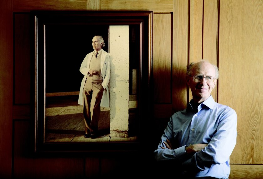 Dr. Peter Salk of La Jolla, one of Dr. Jonas Salk's sons, stands near a photo of his famous father at the Salk Institute for Biological Studies in La Jolla. The elder Salk discovered and developed the first successful polio vaccine.