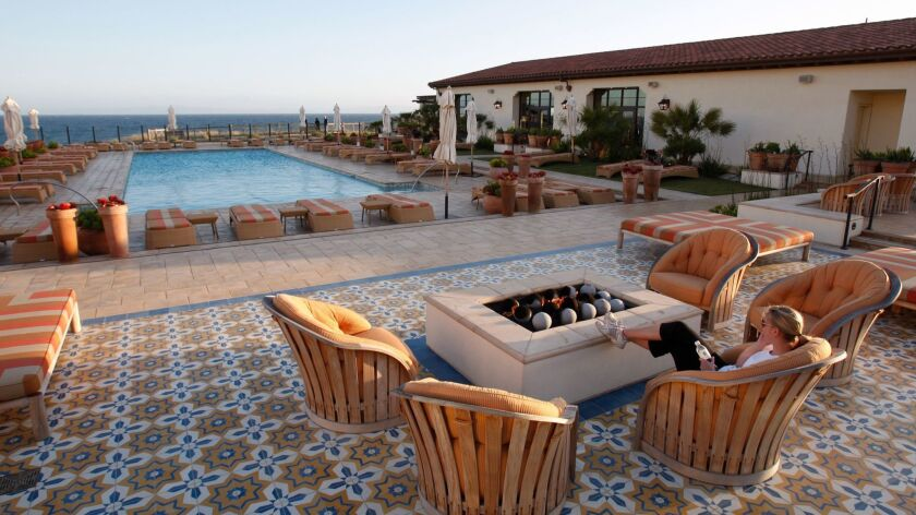 A woman relaxes by the fire pit overlooking the swimming pool and ocean at the Terranea Resort in Rancho Palos Verdes.