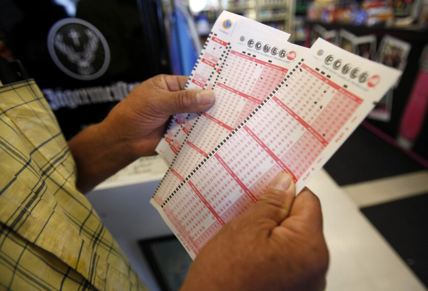 In this file photo from 2013, Rafael Moreno picks his lucky numbers to play the Powerball.