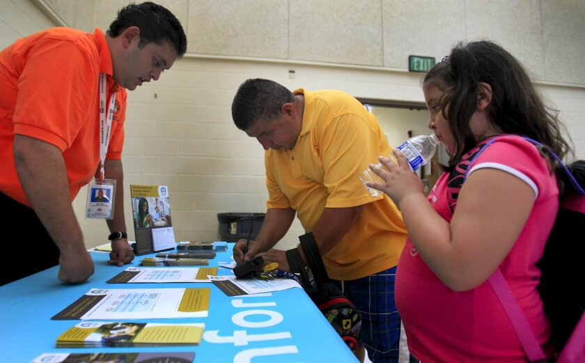 Mao Nieto, left, of the La Maestra Community Health Centers, promoting the new Covered California health exchange during the 79th District Health Fair and Back to School Kickoff the George Stevens Senior Center, talks with Jose Aguilar, center, as his daughter, seven-year-old Angelina Aguilar, righ