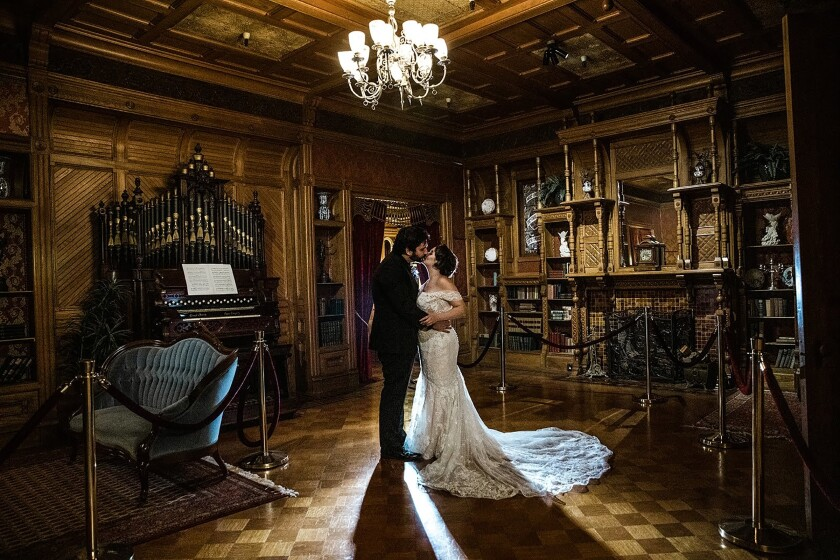 A bride and groom kiss inside a room of the Winchester Mystery House in San Jose.