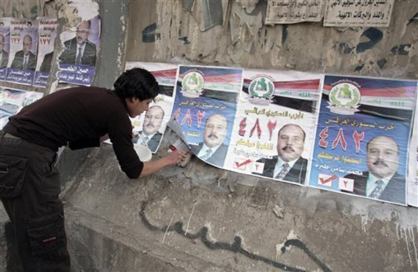 An Iraqi teen puts up campaign posters for the Jan. 31 provincial election in Baghdad, Iraq on Thursday, Jan. 15, 2009. (AP Photo/Karim Kadim)