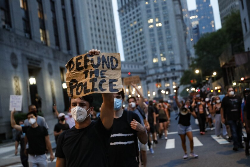 """FILE - In this Thursday, July 30, 2020, file photo, a demonstrator holds a sign that reads """"Defund the Police,"""" during a protest march in support of the Black Lives Matter movement and other groups, in New York. The racial justice protests following the death of George Floyd spurred calls to """"defund the police"""" in cities across the country, a priority for activists that has now become a central point in the presidential contest. (AP Photo/John Minchillo, File)"""