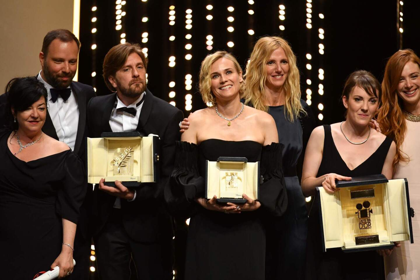 Best screenplay co-laureates directors Lynne Ramsay and director Yorgos Lanthimos, Palme d'Or laureate director Ruben Ostlund, best actress prize laureate Diane Kruger, actress and President of the Camera d'Or jury Sandrine Kiberlain, Camera d'Or laureate director Leonor Serraille and actress Laetiti Dosch pose on stage at the end of the closing ceremony.