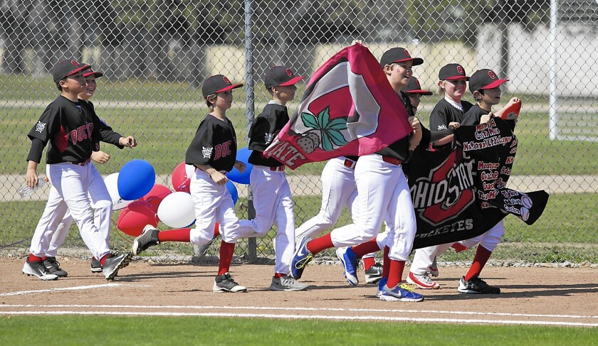 Members of the Minor A division Buckeyes parade their banner during Costa Mesa National Little League opening ceremonies.