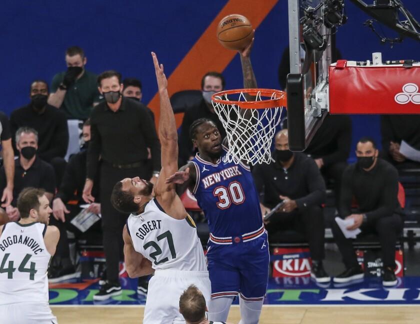 New York Knicks forward Julius Randle (30) dunks next to Utah Jazz center Rudy Gobert (27) during the first half of an NBA basketball game Wednesday, Jan. 6, 2021, in New York. (Wendell Cruz/Pool Photo via AP)