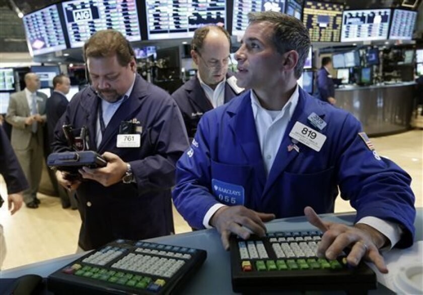 Specialist Anthony Rinaldi, right, works with traders on the floor of the New York Stock Exchange Friday, July 5, 2013.  Concern over China's slowdown weighed on Asian stocks Monday July 8, 2013 while European markets regained their footing after last week's stronger-than-expected U.S. jobs report.