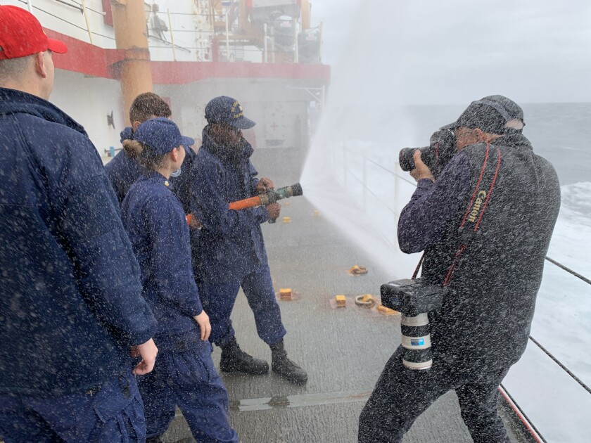 L.A. Times photographer Brian van der Brug gets soaked while shooting Coast Guard crew members training to fight fires aboard the Polar Star.