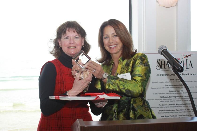 La Jolla Light executive editor Susan DeMaggio accepts the Spirit of Giving Award from Lisa Betyar.